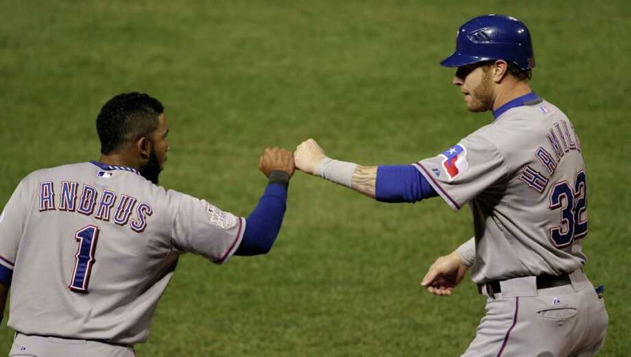 Texas Rangers' Josh Hamilton (32) is congratulated by Elvis Andrus (1) after scoring during the first inning of Game 7 of baseball's World Series against the St. Louis Cardinals Friday, Oct. 28, 2011, in St. Louis. (AP Photo/Paul Sancya) Photo: Paul Sancya, Associated Press / AP