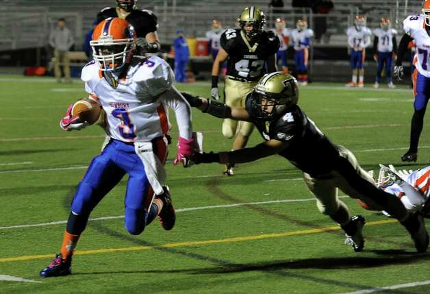 Danbury's #3 James Harington evades Trumbull's #4 Jaff Jarboe on his way to the team's first touchdown, during boys football action in Trumbull, Conn. on Thursday October 28, 2011. Photo: Christian Abraham / Connecticut Post