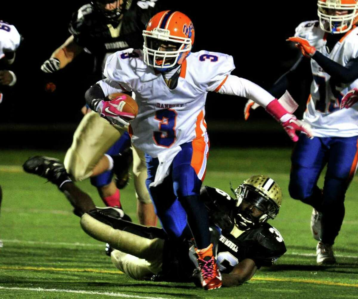 Danbury's #3 James Harington leaves behind Trumbull's #36 Seon Ramsay as he carries the ball, during boys football action in Trumbull, Conn. on Thursday October 28, 2011.