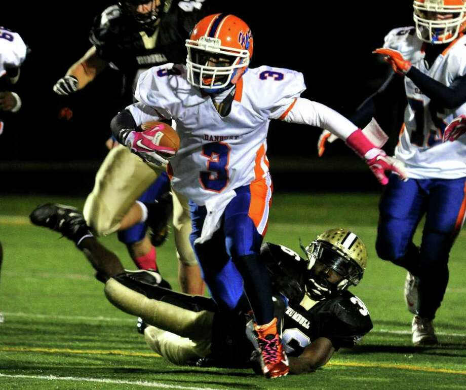 Danbury's #3 James Harington leaves behind Trumbull's #36 Seon Ramsay as he carries the ball, during boys football action in Trumbull, Conn. on Thursday October 28, 2011. Photo: Christian Abraham / Connecticut Post