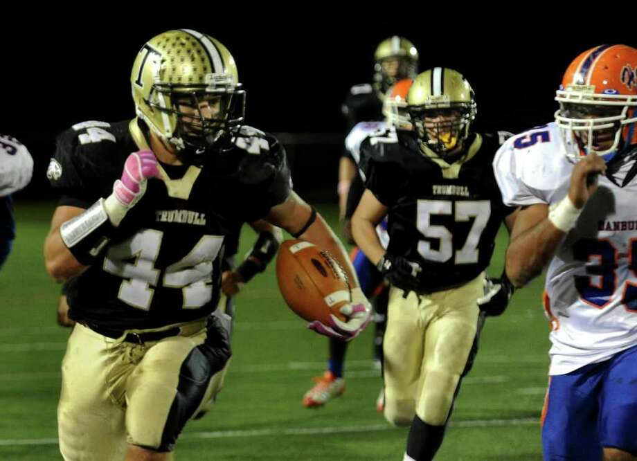 Trumbull's #44 Don Cherry, left, carries the ball, during boys football action against Danbury in Trumbull, Conn. on Thursday October 28, 2011. Photo: Christian Abraham / Connecticut Post