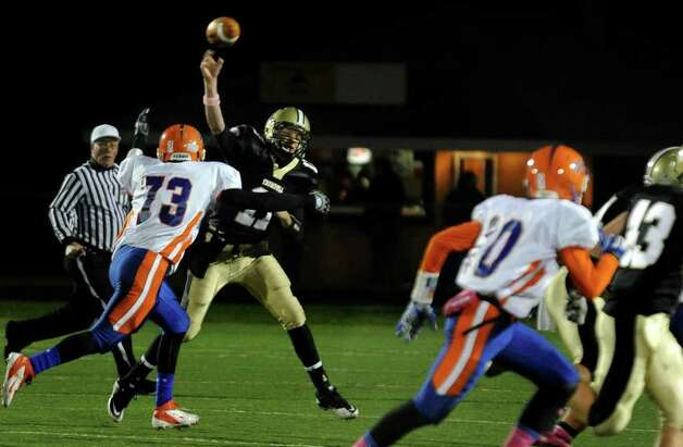 Danbury's #73 William Jack, left, bears down on Trumbull QB Nick Roberts as he makes a pass, during boys football action in Trumbull, Conn. on Thursday October 28, 2011. Photo: Christian Abraham / Connecticut Post