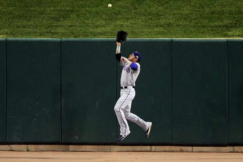 ST LOUIS, MO - OCTOBER 28: Josh Hamilton #32 of the Texas Rangers makes a catch at the wall on a ball hit by Yadier Molina #4 of the St. Louis Cardinals to end the first inning during Game Seven of the MLB World Series at Busch Stadium on October 28, 2011 in St Louis, Missouri. Photo: Doug Pensinger, Getty / 2011 Getty Images
