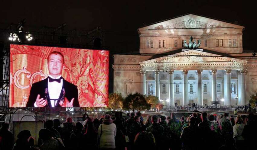 People watch a live broadcast of Russian President Dmitry Medvedev's speech at the gala opening of the Bolshoi Theater in Moscow, Russia, Friday, Oct. 28, 2011.