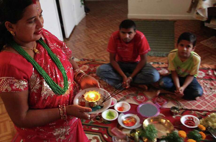 Bhutanese refugee Lachi Kheral walks in a circle with a candle to protect people inside circle during the Bhai Tika. Photo: Mayra Beltran, Houston Chronicle / © 2011 Houston Chronicle