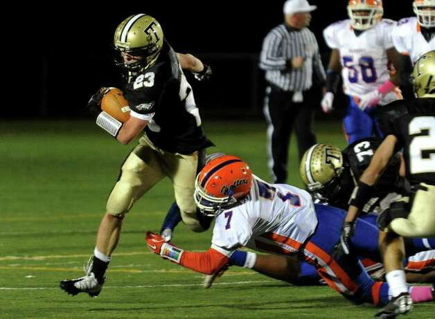 Trumbull's #23 Michael Uus gets snagged by Danbury's #7 Corey Chaffee, during boys football action in Trumbull, Conn. on Thursday October 28, 2011. Photo: Christian Abraham / Connecticut Post