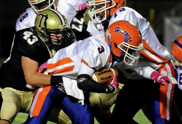 Trumbull's #43 Matt Kelley, left, works to take down Danbury's #3 James Harrington, during boys football action in Trumbull, Conn. on Thursday October 28, 2011. Photo: Christian Abraham / Connecticut Post