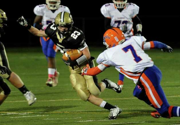 Trumbull's #23 Michael Uus attempts to evade Danbury's #7 Corey Chaffee, during boys football action in Trumbull, Conn. on Thursday October 28, 2011. Photo: Christian Abraham / Connecticut Post