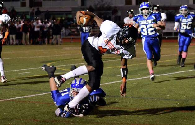Stamford's Bryan Boderick (4) avoids a tackle by Fairfield Ludlowe's John Desmond (71) during the football game at Taft Field at Ludlowe High School on Friday, Oct. 28, 2011. Photo: Amy Mortensen / Connecticut Post Freelance