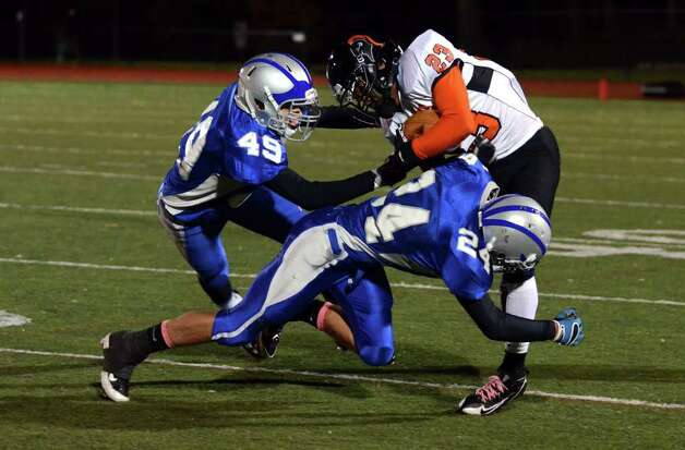 Fairfield Ludlowe's Kyle Dammeyer (49) and Daniel Silvestri (24) tackle Stamford ball carrier Jamor Thompson (23) during the football game at Taft Field at Ludlowe High School on Friday, Oct. 28, 2011. Photo: Amy Mortensen / Connecticut Post Freelance