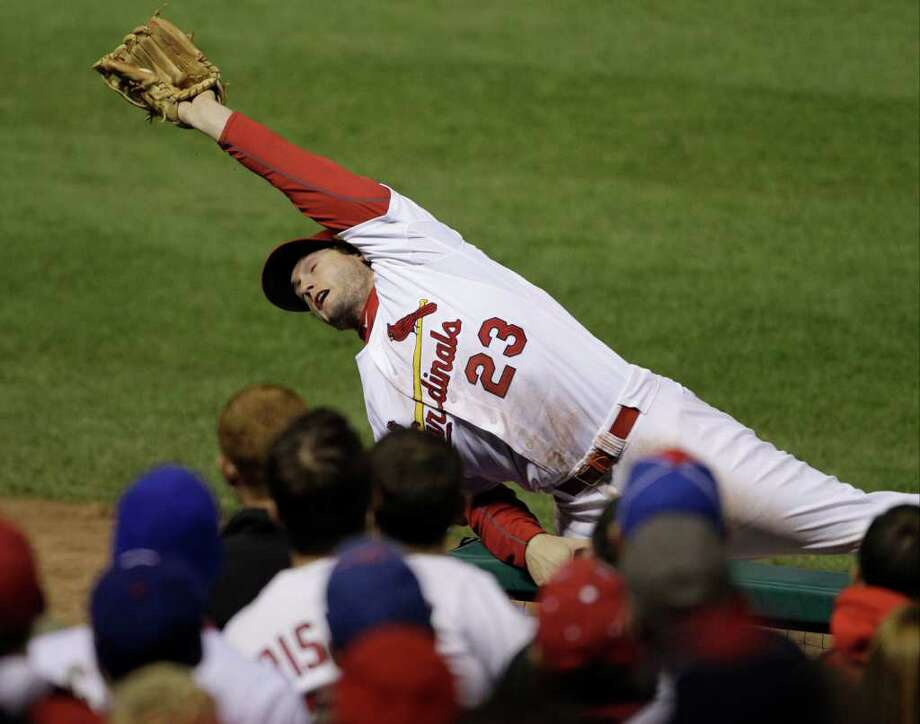 St. Louis Cardinals' David Freese catches a foul ball hit by Texas Rangers' Josh Hamilton during the fifth inning of Game 7 of baseball's World Series Friday, Oct. 28, 2011, in St. Louis. (AP Photo/Paul Sancya) Photo: Paul Sancya, Associated Press / AP