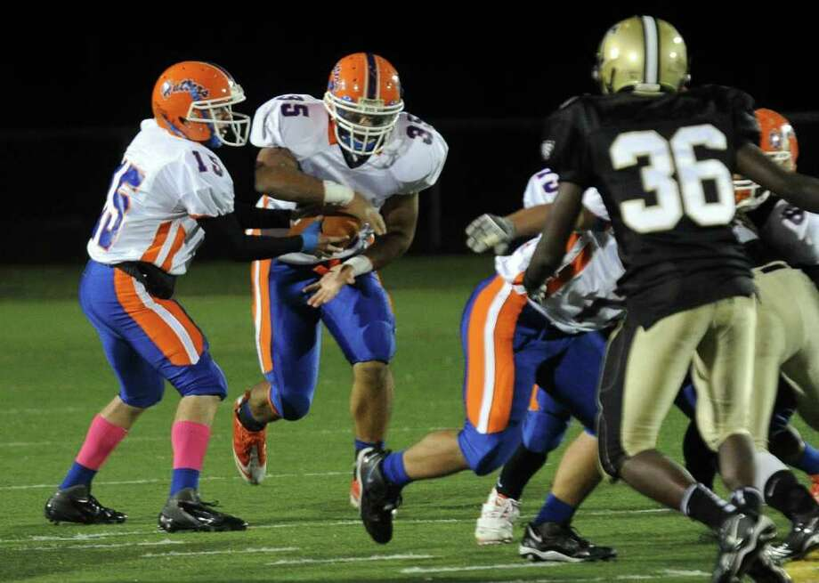 Highlights from boys football action between Trumbull and Danbury in Trumbull, Conn. on Thursday October 28, 2011. Danbury QB #15 Garin Mooney, left, hands the ball off to #35 Austin Calltro. Photo: Christian Abraham / Connecticut Post