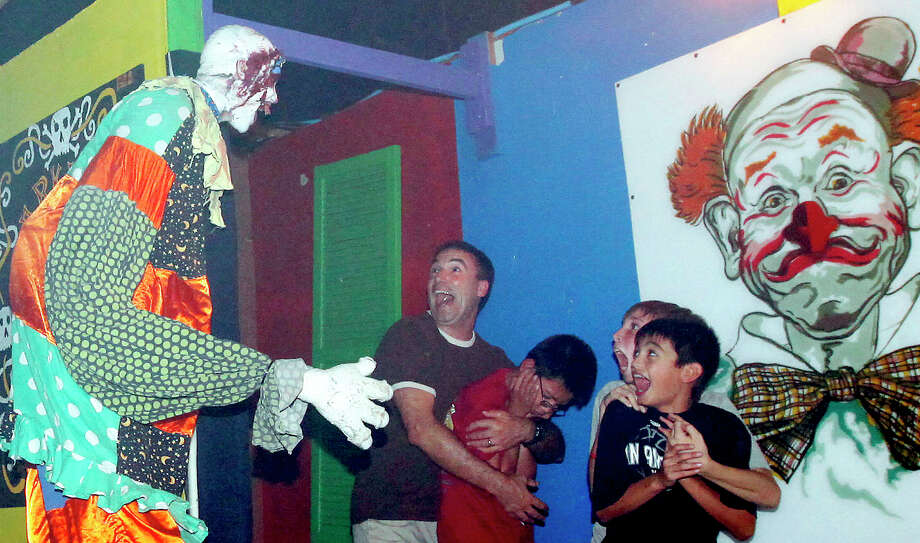 Visitors to Nightmare on Grayson Street get a fright from actor Jerome Barideaux (left) dressed as a seven-foot clown during the haunted house's opening night on Wednesday, Oct. 26, 2011. Kin Man Hui/kmhui@express-news.net Photo: Kin Man Hui, SAN ANTONIO EXPRESS-NEWS / San Antonio Express-News