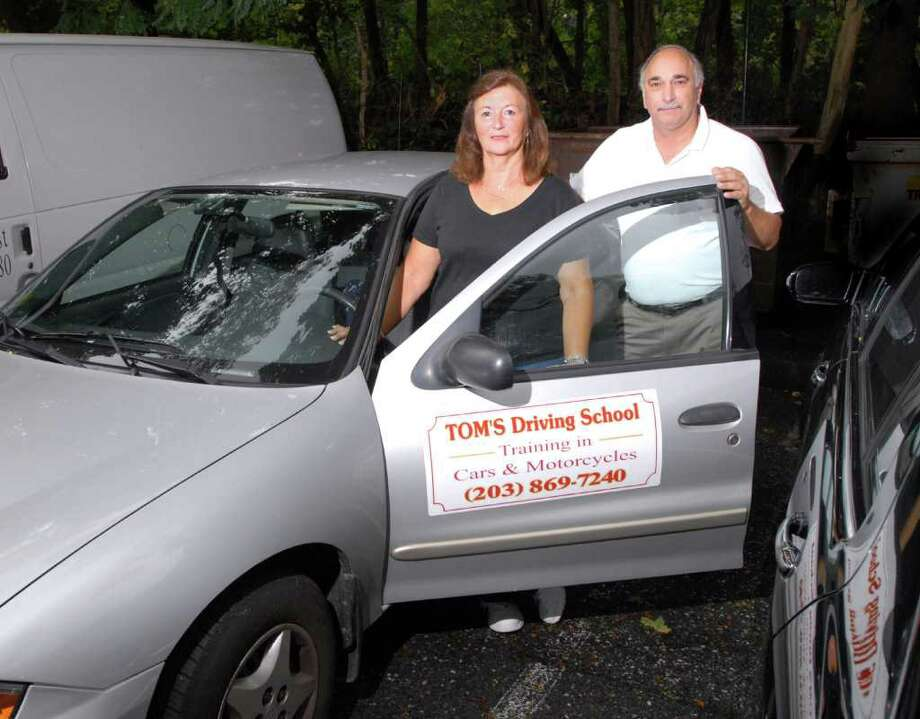 Linda Muccio and her brother, Tom Ferraro, owners of Tom's Driving School, in front of one of their vehicles in the Riverside section of Greenwich, Thursday, Sept. 29, 2011. Photo: Bob Luckey / Greenwich Time