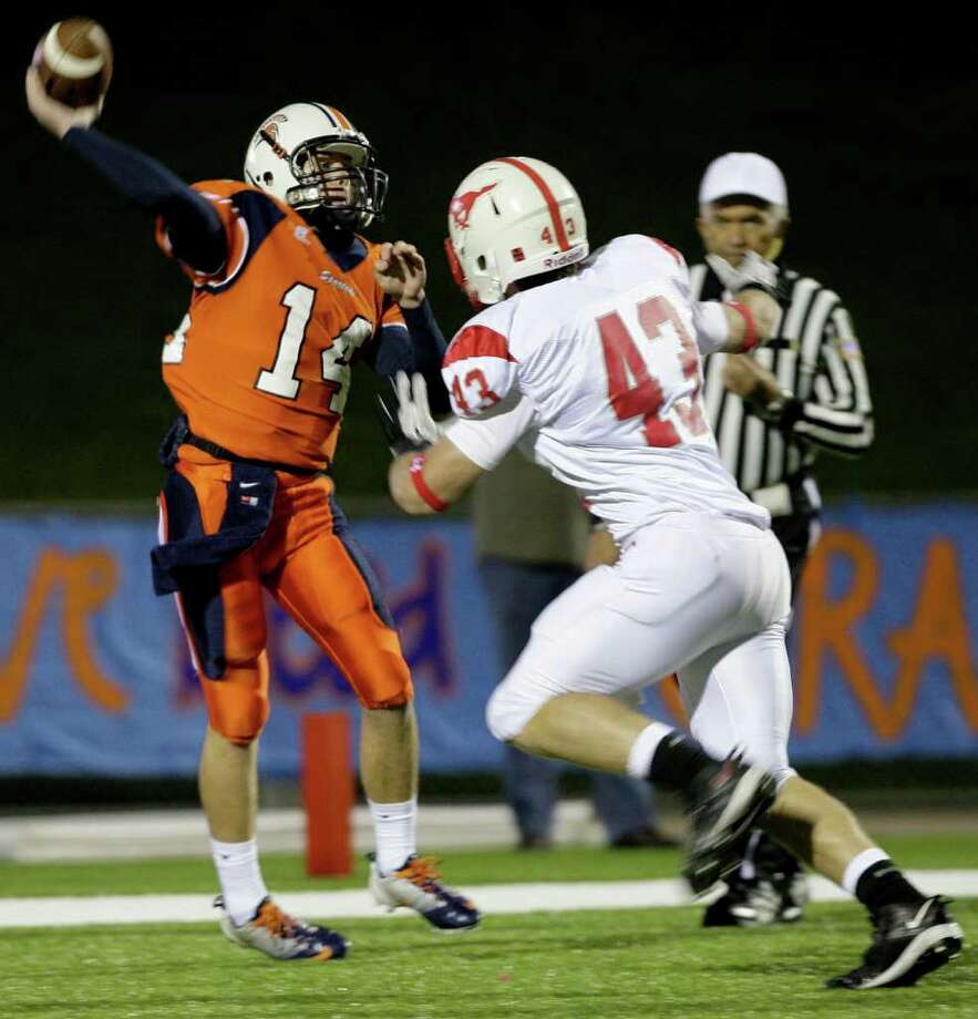 10/28/11: Quarterback Kaleb Morton #14 of Seven Lakes Spartans completes a pass while being pressured by defensive back Brian Womac #43 of Memorial Mustangs in a in district 19-5A high school football game at Rhodes Stadium in Katy, Texas. For the Houston Chronicle: Thomas B. Shea Photo: For The Chronicle: Thomas B. She