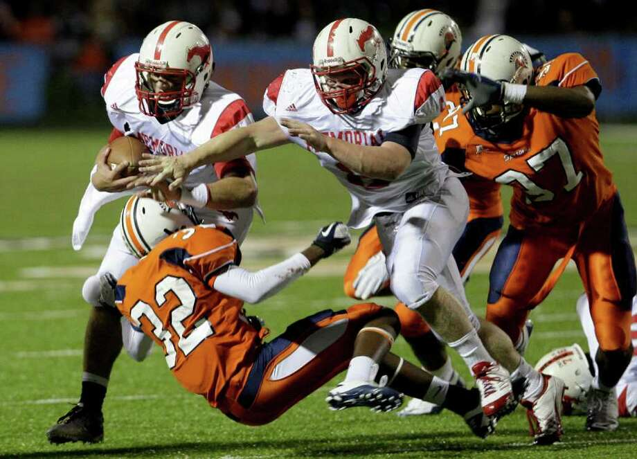 10/28/11: Quarterback Tyler McCloskey #7 of Memorial Mustangs runs over defensive back Daryl Blunt #32 of Seven Lakes Spartans  in a in district 19-5A high school football game at Rhodes Stadium in Katy, Texas. For the Houston Chronicle: Thomas B. Shea Photo: For The Chronicle: Thomas B. She