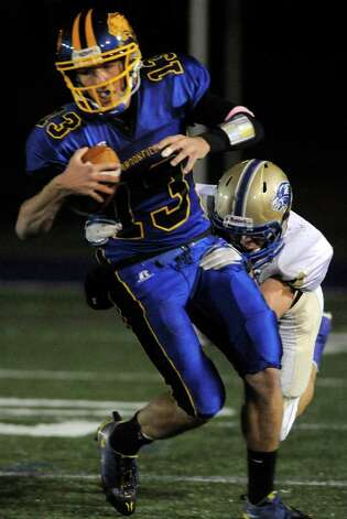 Brookfield quarterback Boeing Brown is brought down by Newtown's Cory Fisher during their game at Brookfield High School on Friday, Oct. 28, 2011. Newtown won 41-0. Photo: Jason Rearick / The News-Times