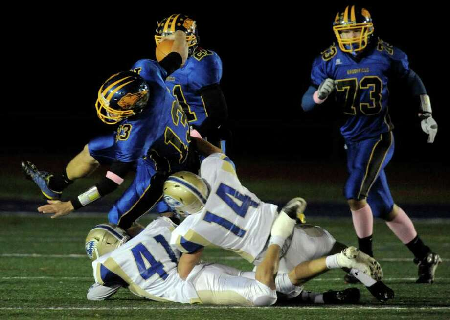 Brookfield quarterback Boeing Brown is brought down by Newtown's Mike Lord(41) and Andrew Cebry(14) during their game at Brookfield High School on Friday, Oct. 28, 2011. Newtown won 41-0. Photo: Jason Rearick / The News-Times