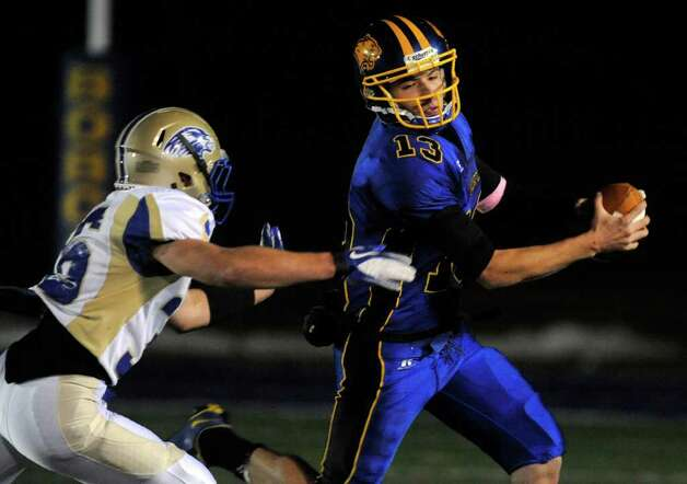 Brookfield quarterback Boeing Brown, right, runs under pressure from Newtown's Cory Fisher during their game at Brookfield High School on Friday, Oct. 28, 2011. Newtown won 41-0. Photo: Jason Rearick / The News-Times