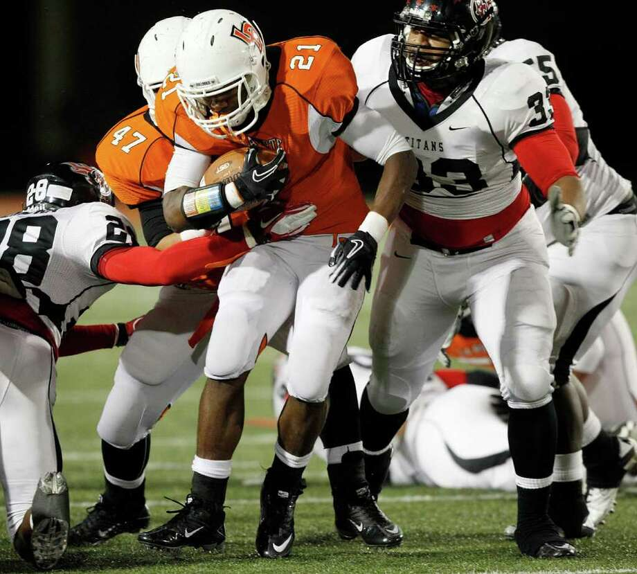 La Porte running Keith Whitely #21 is tackled by Port Arthur Memorial's Darius Lemora #28 and Matthew Romar #33 during a high school football game between Port Arthur Memorial and La Porte Friday, October 28 in Laporte, Texas. Photo: Bob Levey, Houston Chronicle / ©2011 Bob Levey