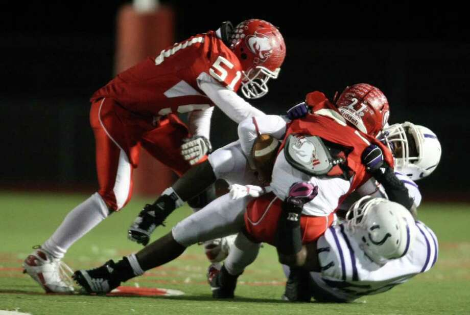 Crosby's Austin Walter (27) is tackled by Dayton defenders during the first half of a District 19-4A high school football game, Friday, October 28, 2011 at Cougar Stadium in Crosby. Photo: Eric Christian Smith, For The Chronicle