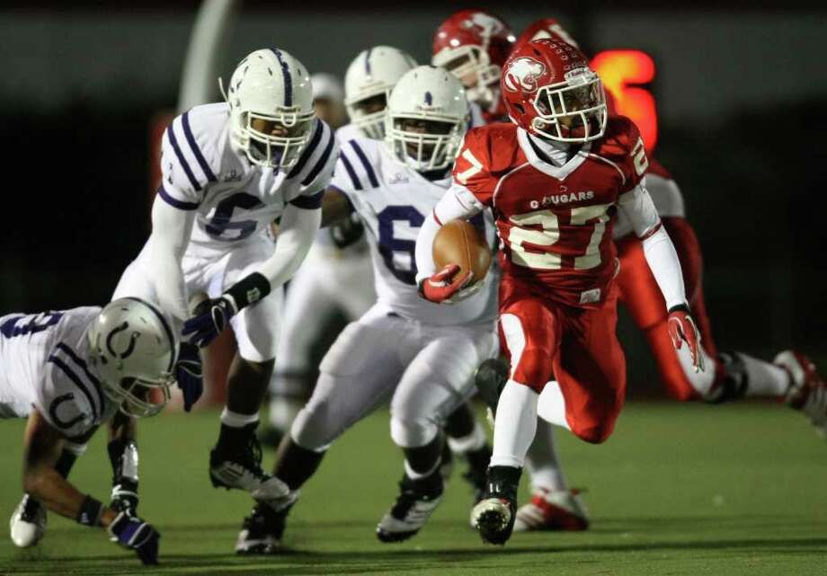 Crosby's Austin Walter scampers past Dayton defenders during the first half of a District 19-4A high school football game, Friday, October 28, 2011 at Cougar Stadium in Crosby. Photo: Eric Christian Smith, For The Chronicle