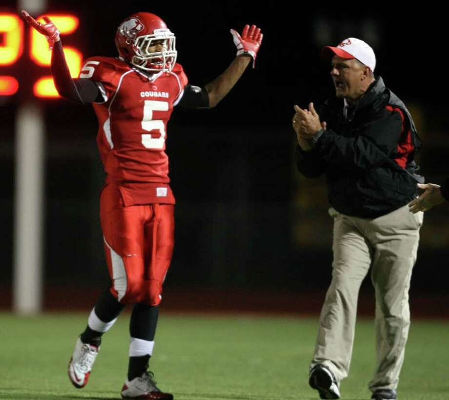 Crosby's Donovan Starks (5) gestures towards the crowd after an offsides penalty went against Dayton as secondary coach Paul Walker looks on during  the first half of a District 19-4A high school football game, Friday, October 28, 2011 at Cougar Stadium in Crosby. Photo: Eric Christian Smith, For The Chronicle