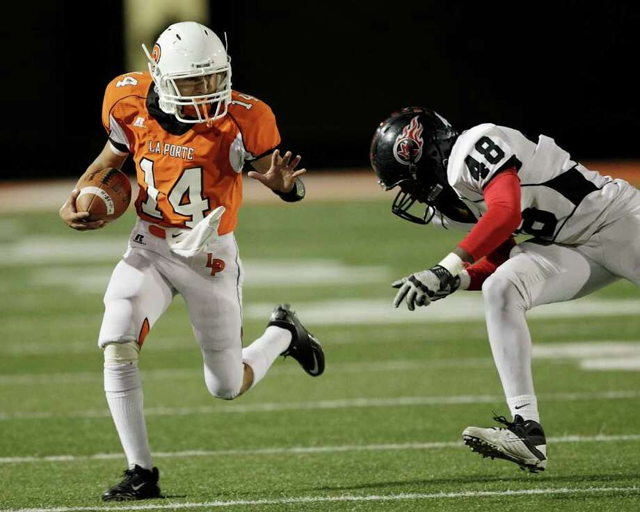 La Porte quarterback Josh Vidales #14 attepts to avoid a tackle from Port Arthur Memorial's Melbroderick Matthews #48 during a high school football game between Port Arthur Memorial and La Porte Friday, October 28 in Laporte, Texas. Photo: Bob Levey, Houston Chronicle / ©2011 Bob Levey