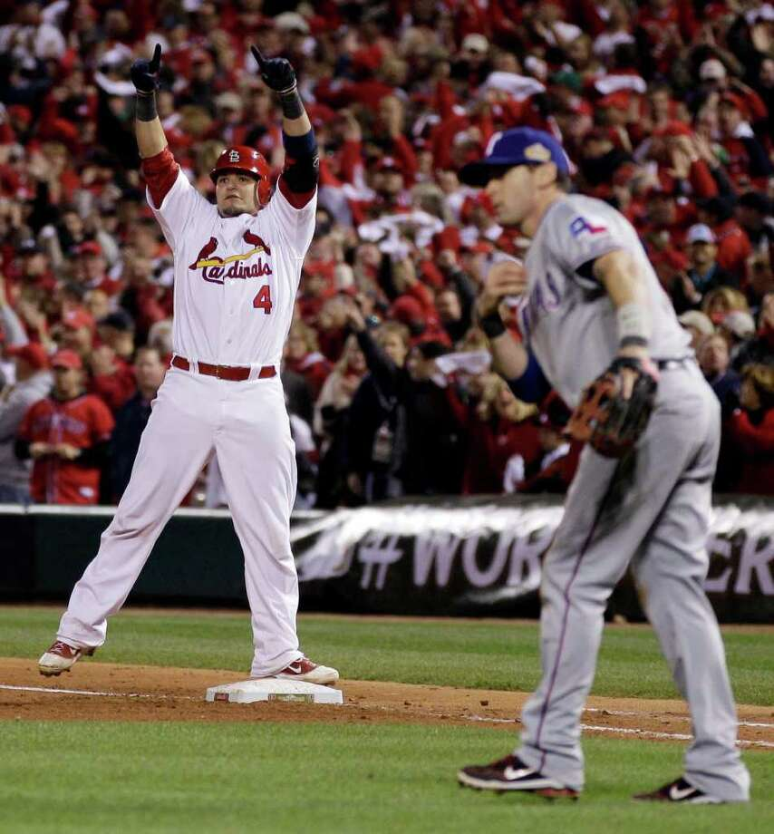 St. Louis Cardinals' Yadier Molina reacts in front of Texas Rangers' Michael Young after Molina hit an RBI single during the seventh inning of Game 7 of baseball's World Series Friday, Oct. 28, 2011, in St. Louis. (AP Photo/Matt Slocum) Photo: Matt Slocum, Associated Press / AP
