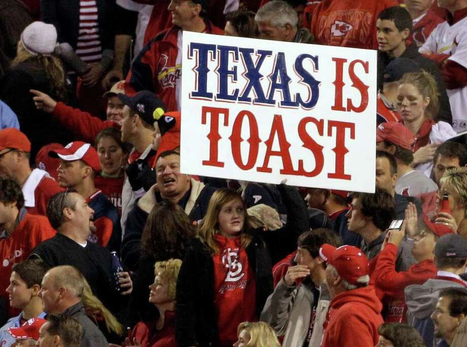 A fan holds up a sign during the seventh inning of Game 7 of baseball's World Series between the St. Louis Cardinals and the Texas Rangers Friday, Oct. 28, 2011, in St. Louis. (AP Photo/Paul Sancya) Photo: Paul Sancya, Associated Press / AP