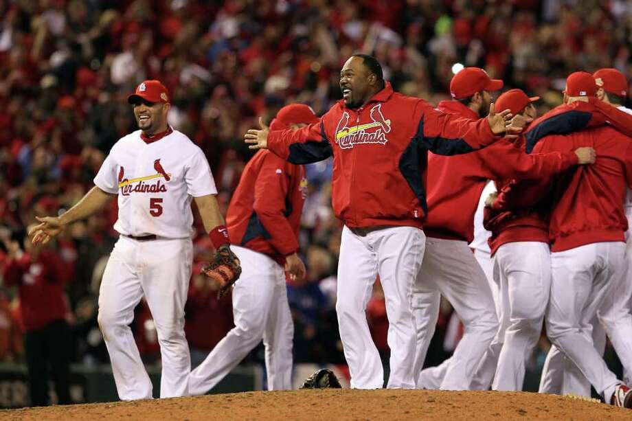 ST LOUIS, MO - OCTOBER 28:  Albert Pujols #5 and Arthur Rhodes #53 of the St. Louis Cardinals celebrate after defeating the Texas Rangers 6-2 to win the World Series in Game Seven of the MLB World Series at Busch Stadium on October 28, 2011 in St Louis, Missouri. Photo: Jamie Squire, Getty / 2011 Getty Images