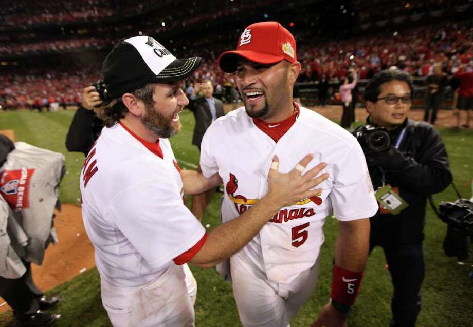 ST LOUIS, MO - OCTOBER 28:  (L-R) Lance Berkman #12 and Albert Pujols #5 of the St. Louis Cardinals celebrate after defeating the Texas Rangers 6-2 to win the World Series in Game Seven of the MLB World Series at Busch Stadium on October 28, 2011 in St Louis, Missouri. Photo: Jamie Squire, Getty / 2011 Getty Images
