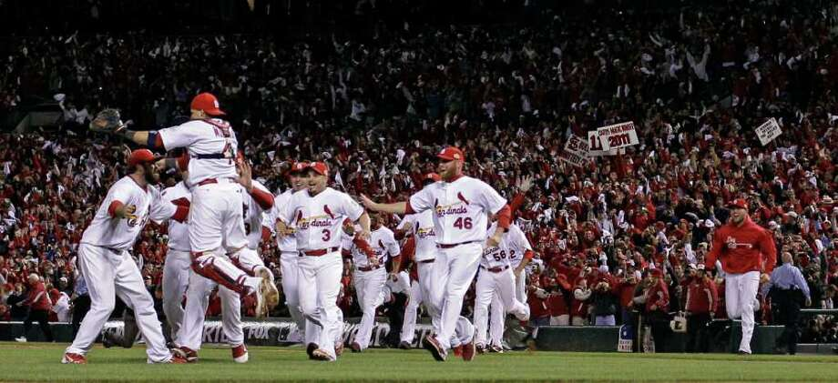 The St. Louis Cardinals celebrate after Texas Rangers' David Murphy flies out to end Game 7 of baseball's World Series Friday, Oct. 28, 2011, in St. Louis. The Cardinals won 6-2 to win the series.  (AP Photo/Matt Slocum) Photo: Matt Slocum, Associated Press / AP