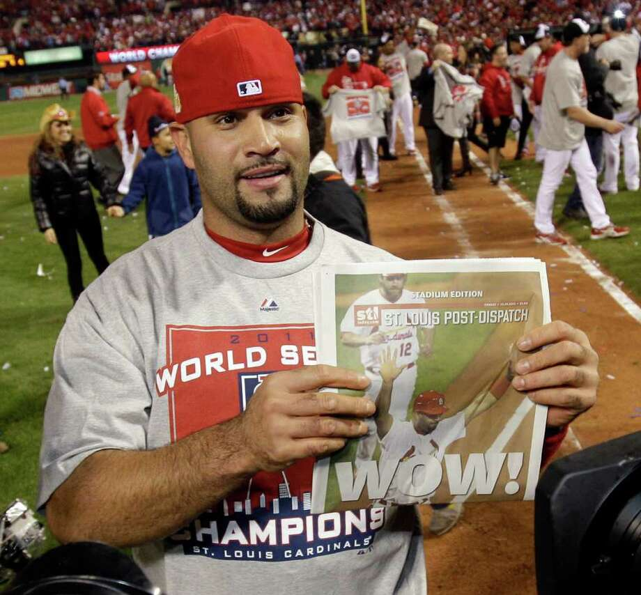 St. Louis Cardinals' Albert Pujols holds up a newspaper after Game 7 of baseball's World Series against the Texas Rangers Friday, Oct. 28, 2011, in St. Louis. The Cardinals won 6-2 to win the series.  (AP Photo/Matt Slocum) Photo: Matt Slocum, Associated Press / AP