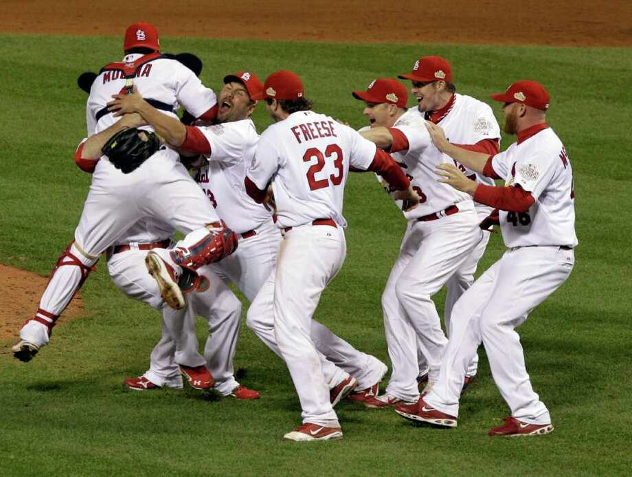 The St. Louis Cardinals celebrate after Texas Rangers' David Murphy flies out to end Game 7 of baseball's World Series Friday, Oct. 28, 2011, in St. Louis. The Cardinals won 6-2 to win the series. (AP Photo/Paul Sancya) Photo: Paul Sancya, Associated Press / AP
