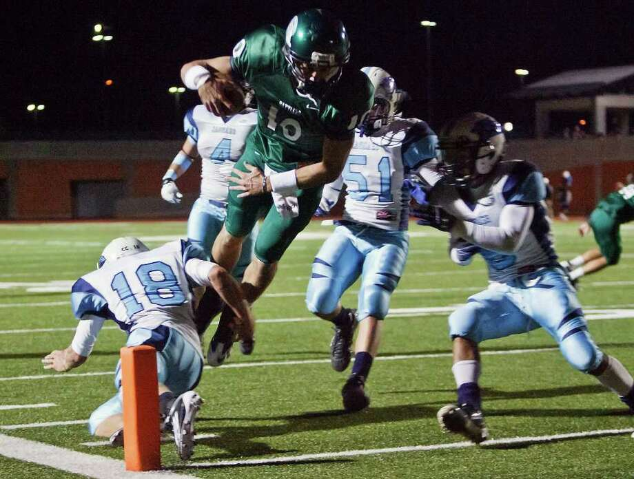 Reagan quarterback Trevor Knight goes airborne for a five-yard touchdown over Johnson's Kyle Brown (left) during the second quarter of their game at Heroes Stadium on Oct. 28, 2011.  MARVIN PFEIFFER/mpfeiffer@express-news.net Photo: MARVIN PFEIFFER, Express-News / Express-News 2011
