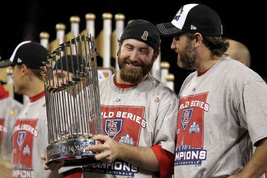 ST LOUIS, MO - OCTOBER 28:  (L-R) Jason Motte #30 and Lance Berkman #12 of the St. Louis Cardinals hold up the World Series trophy after defeating the Texas Rangers 6-2 in Game Seven of the MLB World Series at Busch Stadium on October 28, 2011 in St Louis, Missouri. Photo: Ezra Shaw, Getty / 2011 Getty Images
