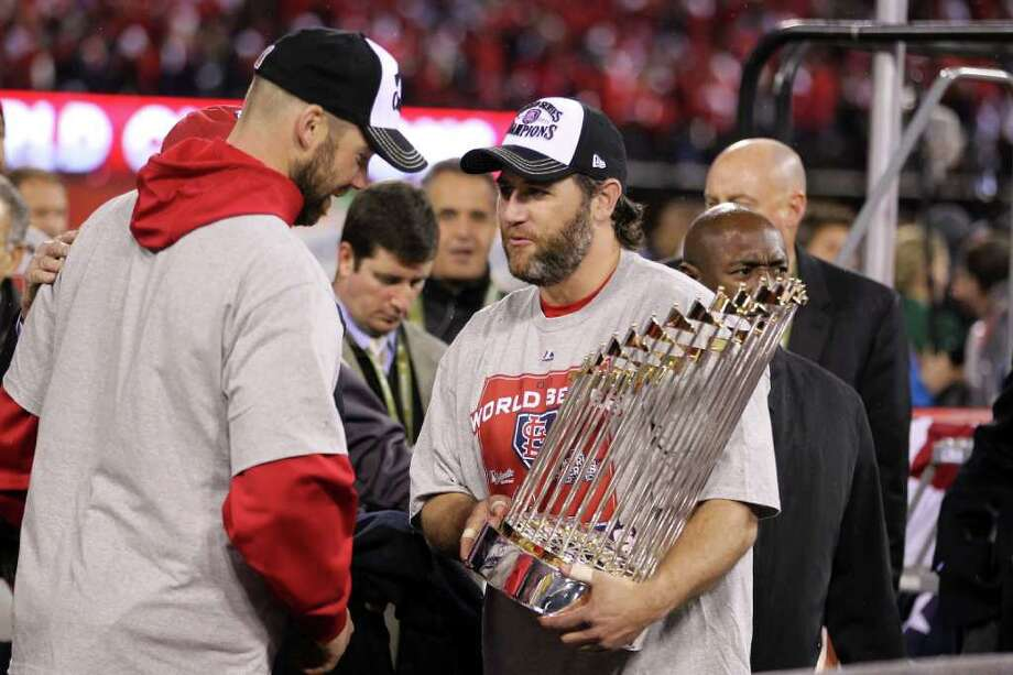 ST LOUIS, MO - OCTOBER 28:  Lance Berkman #12 and Chris Carpenter #29 of the St. Louis Cardinals hold the World Series trophy after defeating the Texas Rangers 6-2 in Game Seven of the MLB World Series at Busch Stadium on October 28, 2011 in St Louis, Missouri. Photo: Ezra Shaw, Getty / 2011 Getty Images
