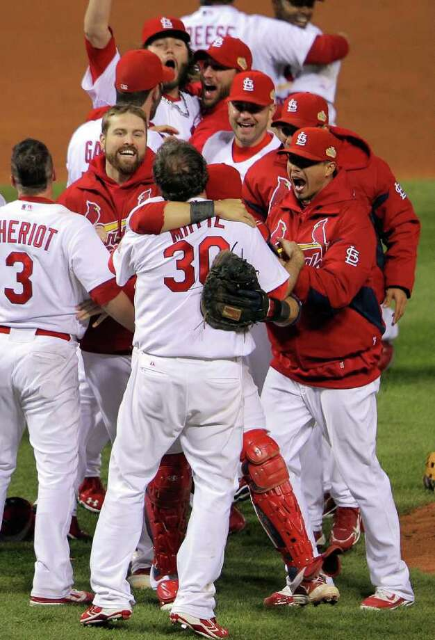 ST LOUIS, MO - OCTOBER 28:  Jason Motte #30 and Yadier Molina #4 of the St. Louis Cardinals celebrate after defeating the Texas Rangers 6-2 to win the World Series in Game Seven of the MLB World Series at Busch Stadium on October 28, 2011 in St Louis, Missouri. Photo: Doug Pensinger, Getty / 2011 Getty Images