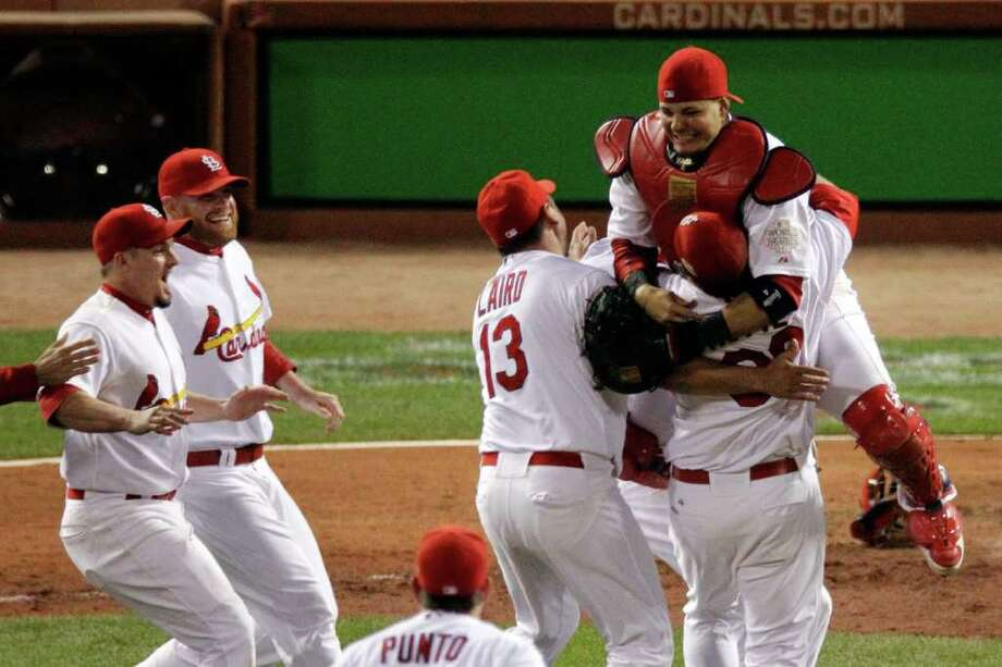 ST LOUIS, MO - OCTOBER 28:  Jason Motte #30, Yadier Molina #4 and Gerald Laird #13 of the St. Louis Cardinals celebrate after defeating the Texas Rangers 6-2 to win the World Series in Game Seven of the MLB World Series at Busch Stadium on October 28, 2011 in St Louis, Missouri. Photo: Rob Carr, Getty / 2011 Getty Images