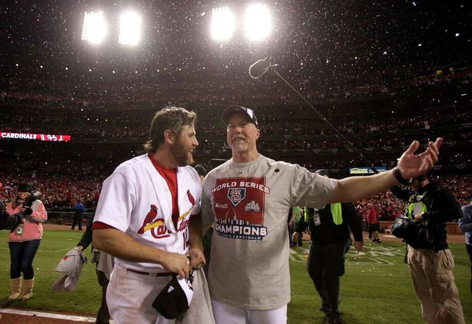 ST LOUIS, MO - OCTOBER 28:  (L-R) Lance Berkman #12 and coach Mark McGuire of the St. Louis Cardinals celebrate after defeating the Texas Rangers 6-2 to win the World Series in Game Seven of the MLB World Series at Busch Stadium on October 28, 2011 in St Louis, Missouri. Photo: Ezra Shaw, Getty / 2011 Getty Images