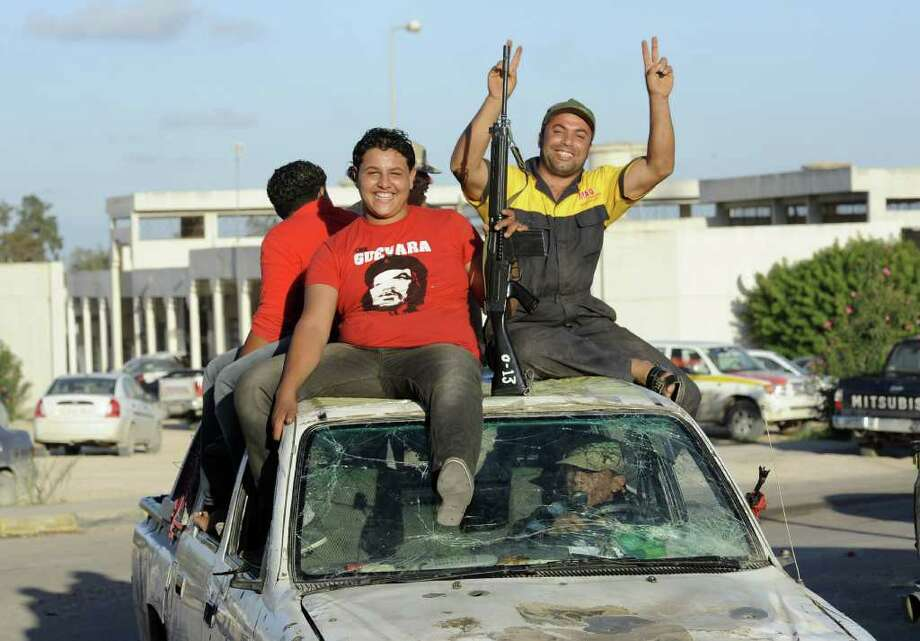 """Libyan National Transitional Council (NTC) fighters sit on top of a pick up truck in the city of Sirte on October 28, 2011. NATO decided to end its mission in Libya on October 31, declaring it fulfilled its """"historic mandate"""" to protect civilians as contact was made with Moamer Kadhafi's fugitive son.   AFP PHOTO/PHILIPPE DESMAZES (Photo credit should read PHILIPPE DESMAZES/AFP/Getty Images) Photo: PHILIPPE DESMAZES / AFP"""