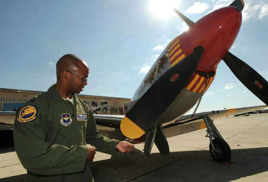 "Air Force Lt. Col. Gavin Marks examines a P-51C Mustang in markings of the 332nd Fighter Group, the ""Tuskegee Airmen"" of World War II fame, at Randolph Air Force Base on Friday, Oct. 28, 2011. Randolph Airshow 2011 begins on Saturday. Photo: BILLY CALZADA, Billy Calzada/gcalzada@express-news.net / gcalzada@express-news.net"