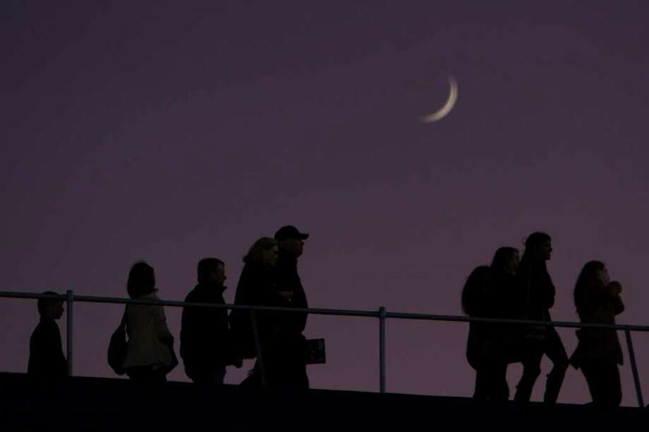 A crescent moon sets over the stadium as fans arrive to watch St. John's face Kinkaid in a high school football game at  Rice Stadium, Friday, Oct. 28, 2011, in Houston. Photo: Smiley N. Pool, Houston Chronicle / © 2011  Houston Chronicle