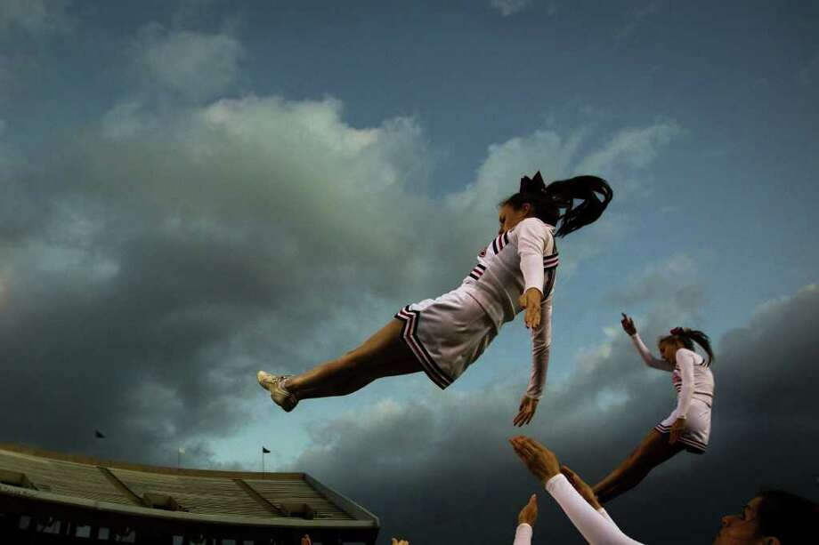 St. Johns cheerleaders warm up against clearing storm clouds before facing Kinkaid in a high school football game at  Rice Stadium, Friday, Oct. 28, 2011, in Houston. Photo: Smiley N. Pool, Houston Chronicle / © 2011  Houston Chronicle
