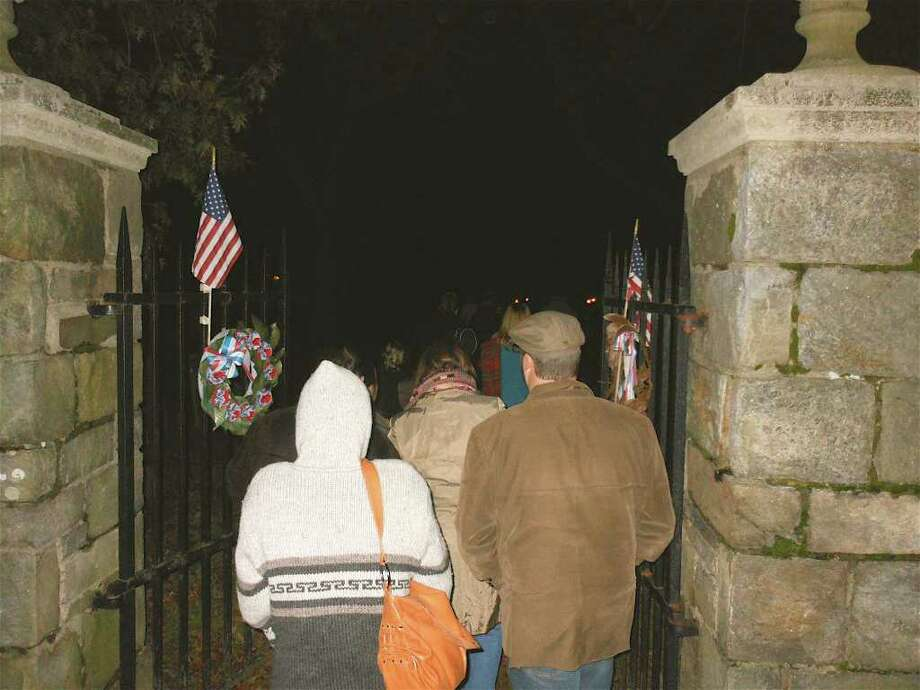 Brave-hearted participants on the annual Spooky Stroll, sponsored Friday by the Fairfield Museum and History Center, walk through the entry gate of the Old Burying Ground where they will meet the resident gravedigger during the pre-Halloween event. Photo: Mike Lauterborn / Fairfield Citizen contributed