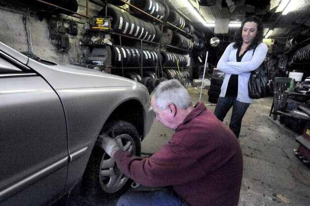 Caludia Sequeira, of Danbury, waits while Bill Lathrop puts all-season tires on her car at McNiffs Tire Shop in Danbury Saturday, Oct. 29, 2011. She said she was preparing for snow. Photo: Michael Duffy