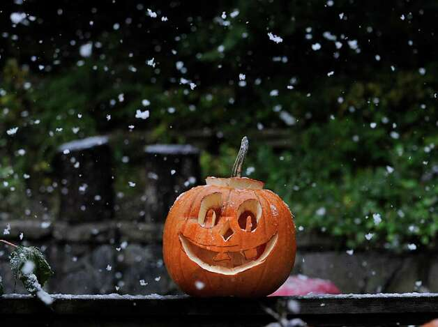 A smiling Jack-o-lantern in the backyard of a Byram Road home during morning snow shower, Saturday Oct. 29. 2011. Photo: Bob Luckey / Greenwich Time