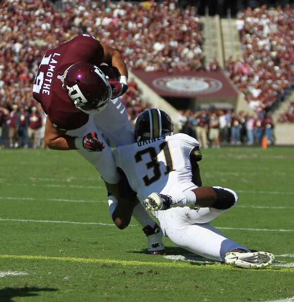 Texas A&M tight end Michael Lamothe (19) barrels over Missouri defensive back E.J. Gaines (31) for a