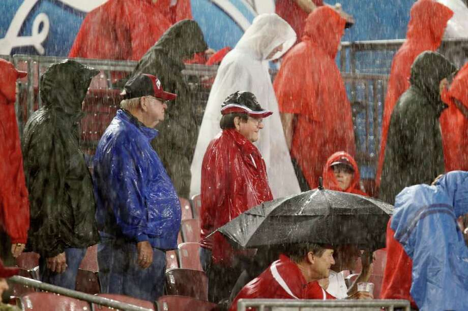 A University of Houston fans brave the rain as U of H plays Rice University during the first quarter of college football game action at Robertson Stadium Thursday, Oct. 27, 2011, in Houston. Photo: James Nielsen, Chronicle / © 2011 Houston Chronicle